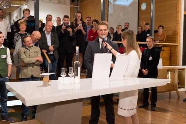"""Daniel Graßmugg erklärt Dr. Sandra Ohms vom ORF und dem Publikum sein Spirituosen-Präsentationsmöbel """"spining spirits"""""""